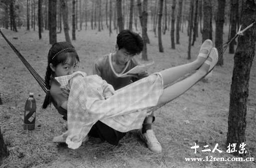 图为90年代情侣,在小树林里,男孩蹲在女友跟前看书学习,女孩子躺